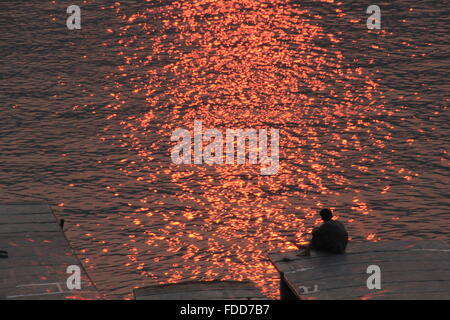 man sitting on a boat and watches the sunset - Stock Photo