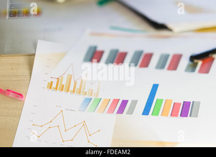 Modern business workplace with tablet, graphs and charts on a desktop. - Stock Photo