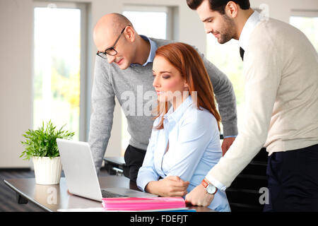 A group of businesspeople having a meeting while sitting around a conference table with a laptop. Teamwork. - Stock Photo