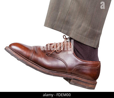 side view of male left leg in brown shoe takes a step isolated on white background - Stock Photo