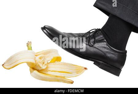male leg in the left black shoe slips on a banana peel isolated on white background - Stock Photo