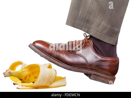male leg in the left brown shoe slips on a banana peel isolated on white background - Stock Photo