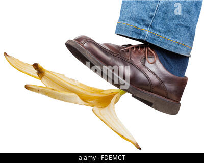 male left leg in jeans and brown shoe slips on a banana peel isolated on white background - Stock Photo