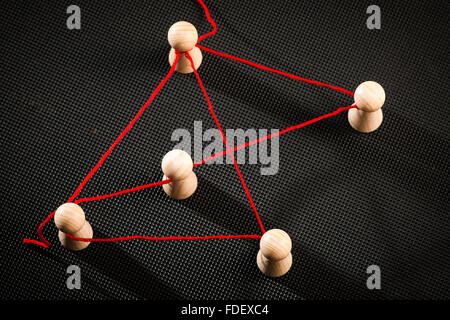 increased detail view with red thread related Ludo game pieces on dark studded surface - Stock Photo