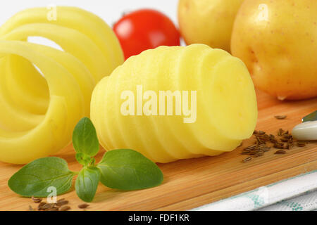 detail of raw potatoes and peel spiral on wooden cutting board - Stock Photo