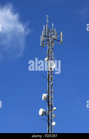 Antenna communications tower against clear blue sky. - Stock Photo