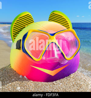 Smiling little man of beach accessories. Ball, flip-flop and diving mask on the beach against a blue sea and sky. - Stock Photo