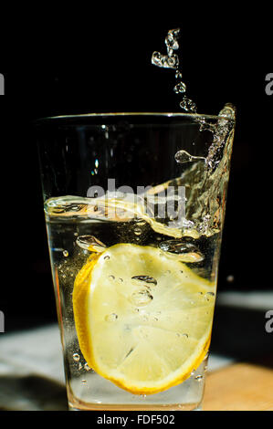 A slice of lemon fallen into a glass of water - Stock Photo