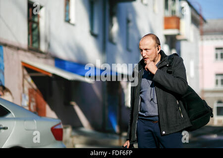 Brutal street photographer with camera in hand strolling city streets, talking on a walkie-talkie handsfree. - Stock Photo