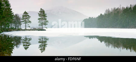 Lochan Eilein in mid-winter, the loch is frozen over. - Stock Photo