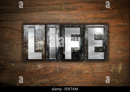 The word 'Life' written in vintage metal letterpress type on an aged wooden background. - Stock Photo