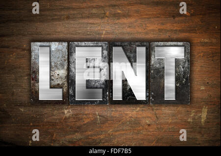The word 'Lent' written in vintage metal letterpress type on an aged wooden background. - Stock Photo