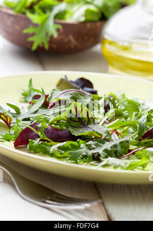 mixture of salad leaves on a plate, olive oil on a wooden background - Stock Photo
