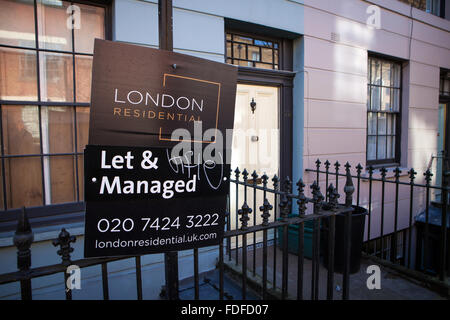 Let & Managed Estate Agent Sign outside terraced housing - Stock Photo