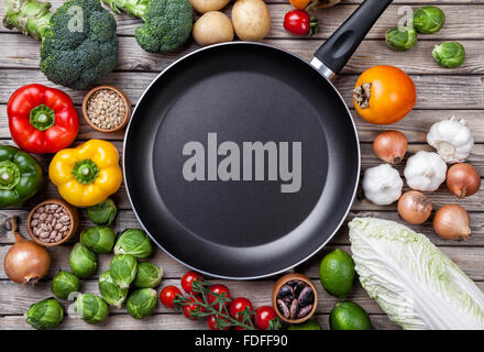 Various vegetables fruits and herbs with a frying pan on wooden background - Stock Photo