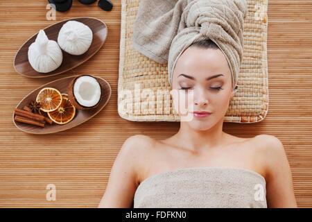 Beautiful young woman relaxing in spa salon - Stock Photo
