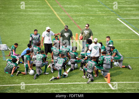 Black coach instructing his black boys football team age 12 on the field. St Paul Minnesota MN USA - Stock Photo