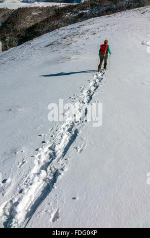 Female in blue with red rucksack snowshoeing, French Pyrenees - Stock Photo