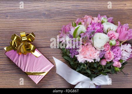 Valentine gift pack with flowers on florist table - Stock Photo