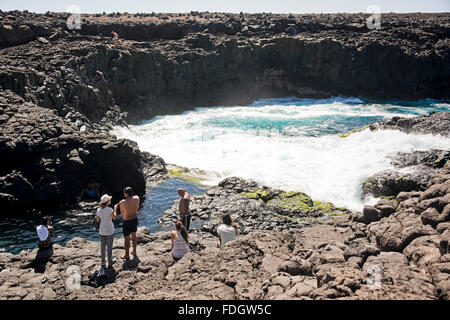 Horizontal view of tourists swimming in the lagoon at Olho Azul, the Blue Eye at Buracona - Stock Photo