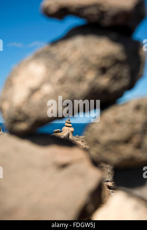 Vertical close up view of pebble towers at Olho Azul, the Blue Eye, in Cape Verde. - Stock Photo