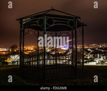 Nightime view over North Plymouth showing the Incinerator, taken through a bandstand in a park. - Stock Photo