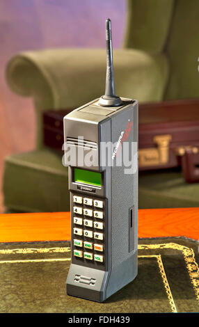 1987 first generation hand mobile cell phone Nokia Mobira Cityman 1320 with 1980's Parker Knoll armchair and 80's - Stock Photo