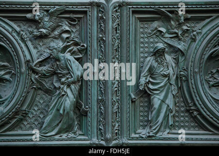 Evangelists Saint Mark and Saint Luke. Detail of the main bronze door of the Milan Cathedral (Duomo di Milano) in - Stock Photo