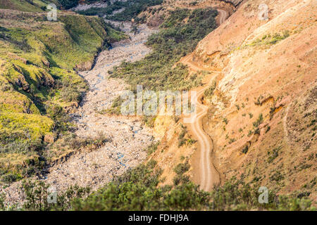 Empty dirt road winding down a mountain in Sani Pass, between South Africa and Lesotho. - Stock Photo