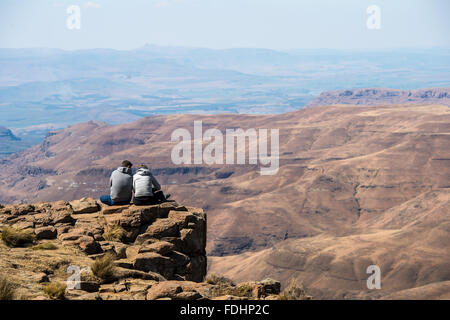 Two people sitting on the edge of a cliff looking over the mountains in Lesotho, Africa