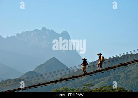 Two farmers walking across a suspension bridge at Kota Belud, Sabah with partial view of Mount Kinabalu at the background. - Stock Photo