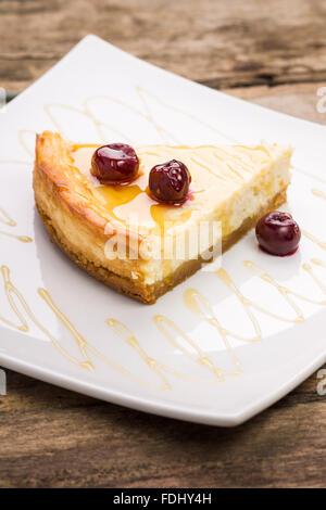 Slice of cheesecake with cherry on white dish. Restaurant dessert background - Stock Photo