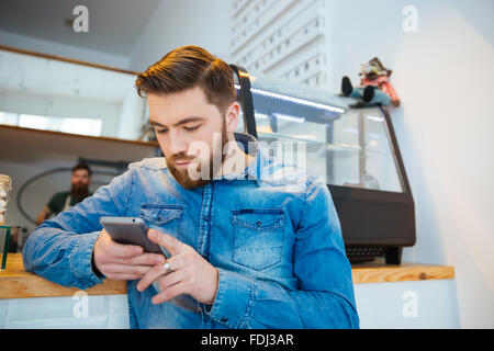 Handsome young man using smartphone in cafe - Stock Photo