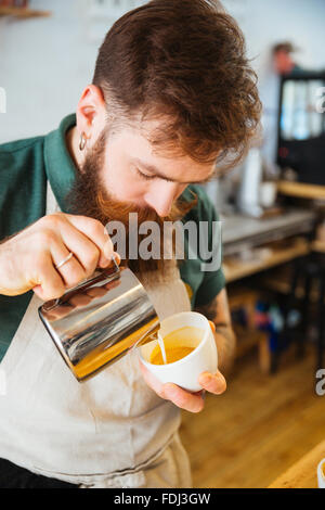 Barista pouring milk into cup of coffee at the coffee shop - Stock Photo