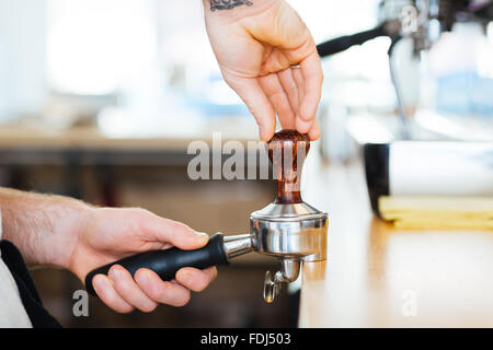 Closeup of portafilter with temper used by hands of barista for pressing ground coffee - Stock Photo