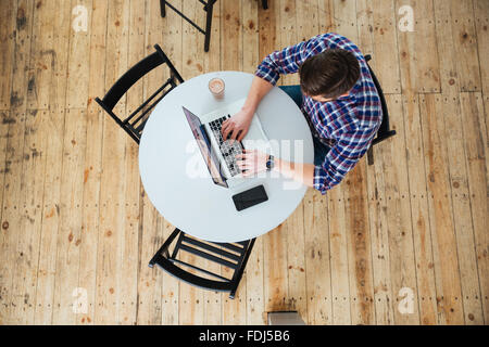 Top view portrait of a man using laptop computer in cafe - Stock Photo