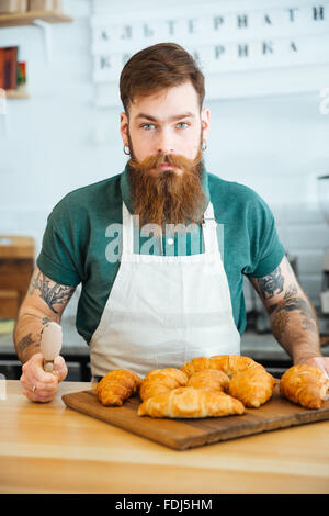 Portrait of handsome bearded man barista with croissants in coffee shop - Stock Photo