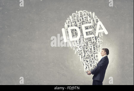 Young businessman carrying in hands bulb idea concept - Stock Photo