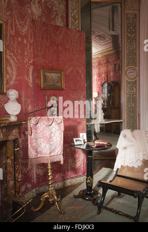 Partial view of the fireplace, and a fire-screen and mirror in the Boudoir at Arlington Court, Devon. The room was - Stock Photo