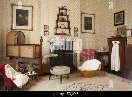 The Day Nursery with a mahogany and wicker cradle and a collection of Victorian toys at Arlington Court, Devon. - Stock Photo
