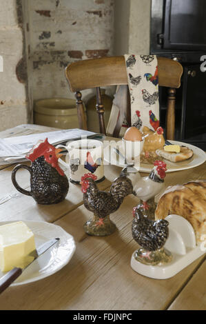 Chicken-themed tableware and tea towel. - Stock Photo