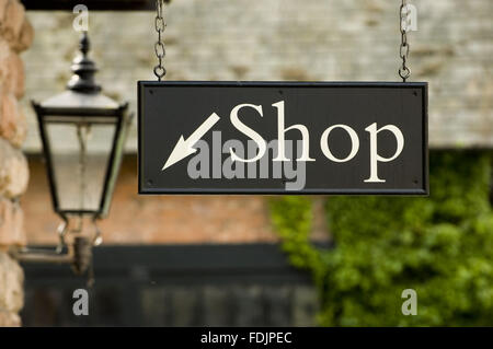 Sign pointing to the shop at Quarry Bank Mill, Styal, Cheshire. The mill was founded in 1784 and produced cotton - Stock Photo