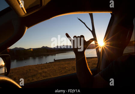 Man sitting in a car making a Shaka sign - Stock Photo