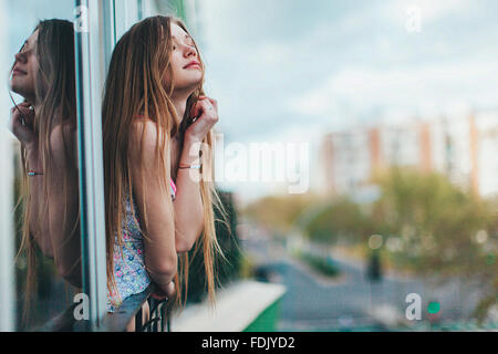 Young woman leaning out of a window in city, Seville, Spain - Stock Photo