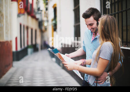 Young couple sightseeing in city with map, Seville, Spain - Stock Photo