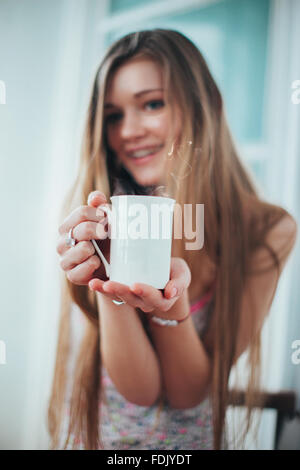 Smiling young woman holding a mug of coffee - Stock Photo