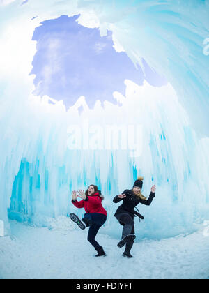 Two girls acting silly under the Dome Room at the Ice Castle in Hawrelak Park, Edmonton, Alberta, Canada. - Stock Photo