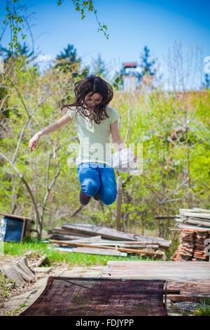 Girl jumping in backyard - Stock Photo
