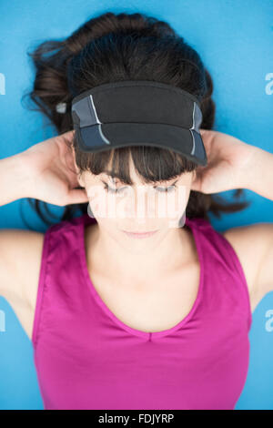 Young woman lying down exercising with hands behind her head - Stock Photo