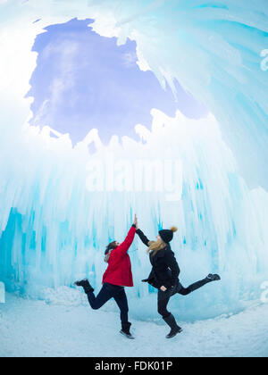 Two friends high five under the Dome Room of the 2015-16 Ice Castle at Hawrelak Park in Edmonton, Alberta, Canada. - Stock Photo